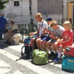 The boys, snarfing sandwiches in the Camões Square, in Lisbon, after arriving by bus.