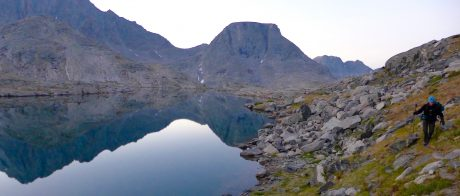 Kathy, scrambling over some rocks and tundra during early morning reflections in one of the lakes of Indian Basin.