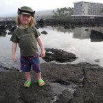 Finis, our 2-year-old, poses on a rock in the ocean tidepools. That's the Outrigger Keauhou Beach Resort in the background.