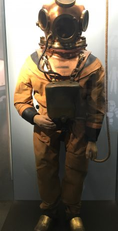 This hose-less diving suit, 1912, consisted of one bottle containing compressed oxygen and a second bottle filled with compressed air. Using a pressure regulating valve, a gas mix was produced which the diver breathed in.  Developed to tether diver to the ship. Divers could dive to 40 meters.